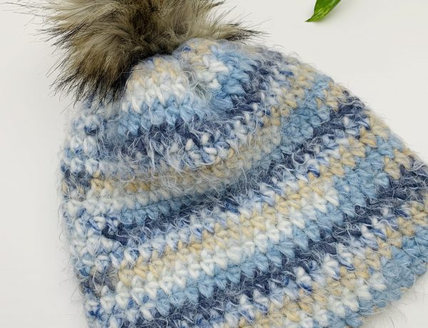 Crochet hat pattern using blue color and attached with pam pom