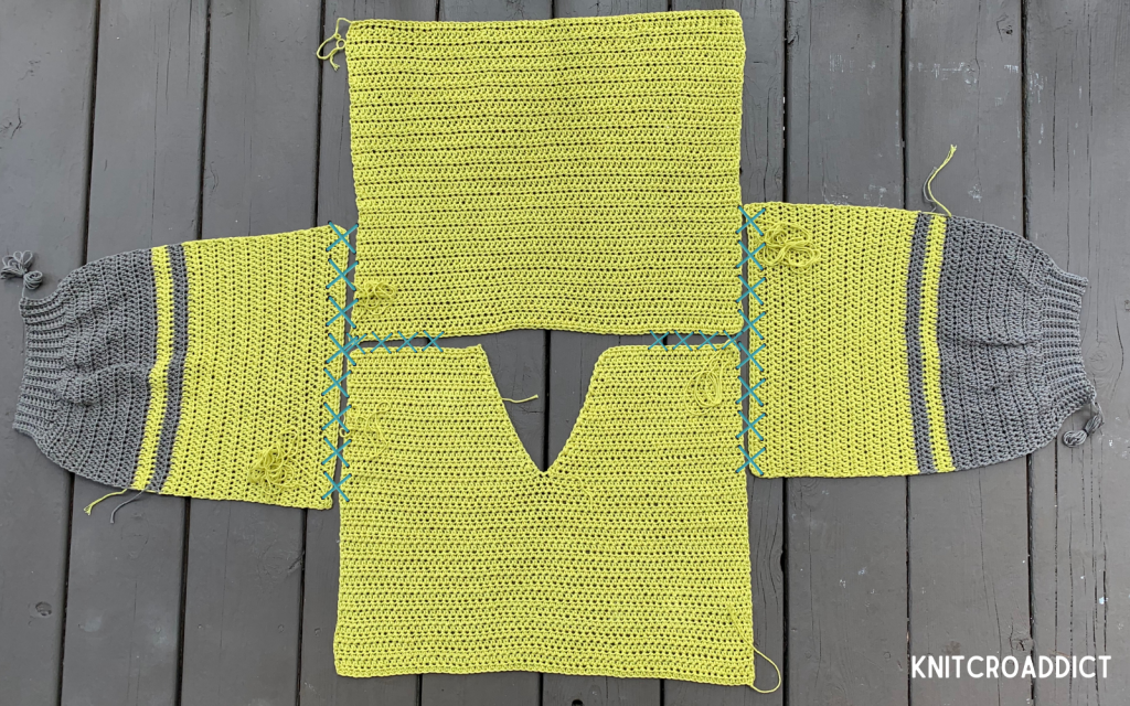 crochet hoodie free pattern and photo tutorial demonstrating how to sew the sleeves to the body panels and sew the shoulder seams