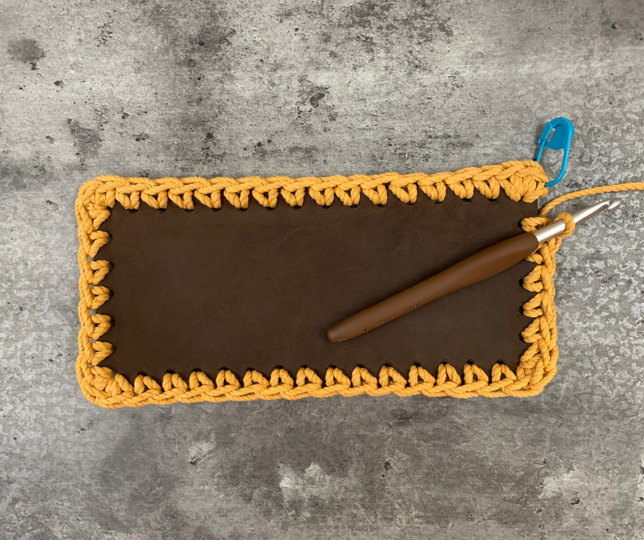 beginning the body of the crochet and leather bag by crocheting into the holes we punched earlier in the leather